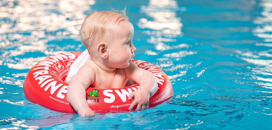Babyschwimmen mit dem Swimtrainer. Baby im Wasser.