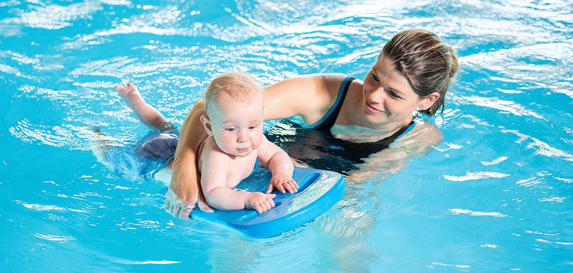 Baby auf Schwimmbrett. Mutter und Baby im Babyschwimmkurs.