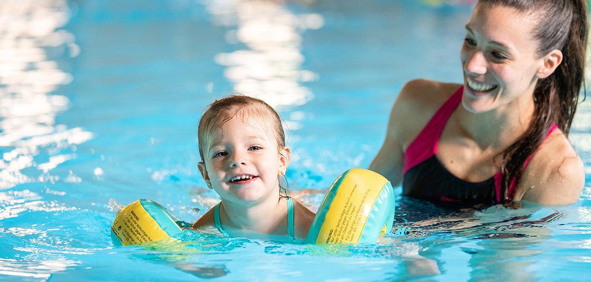 Fröhliches Mädchen mit Mutter beim Babyschwimmen.