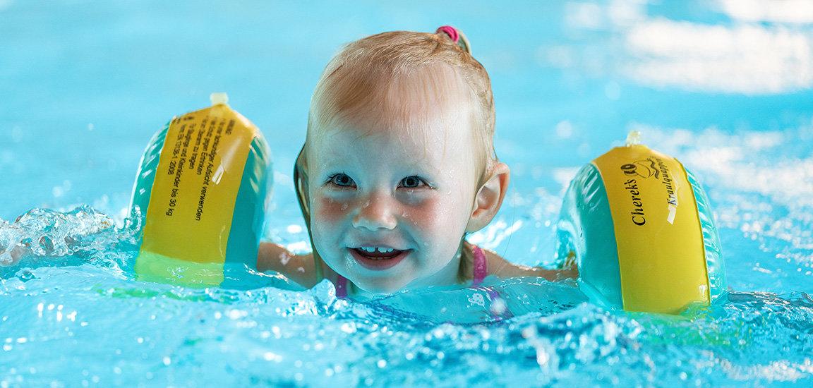 Glückliches Mädchen im Wasser. Kinderschwimmen mit Flügeli.
