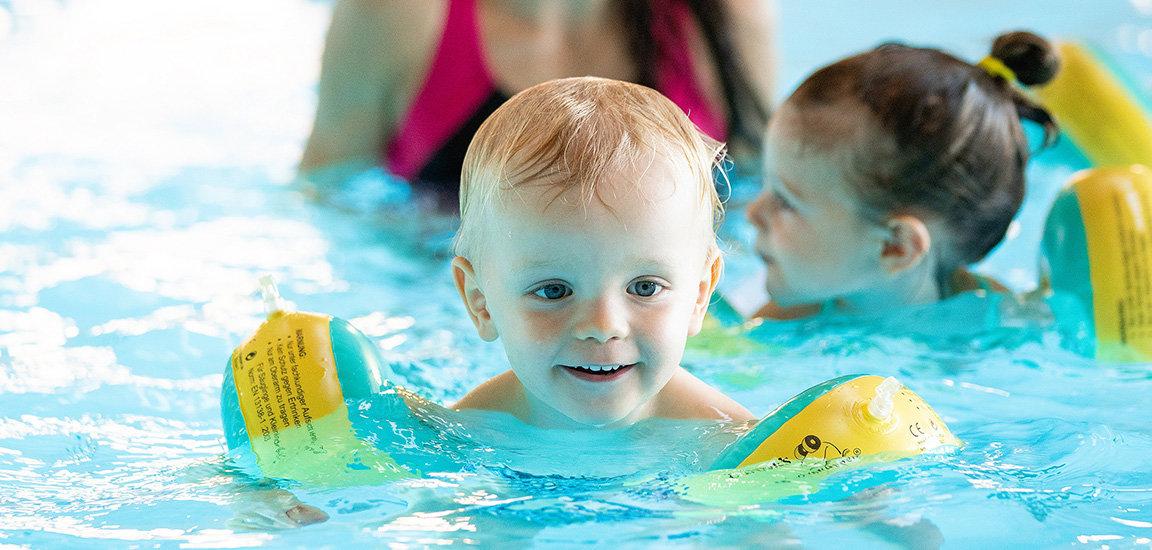 Glückliches Kind im Wasser. Junge beim Babyschwimmen.