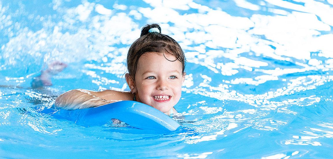 Fröhliches Mädchen im Wasser auf Schwimmbrett im Kinderschwimmkurs.