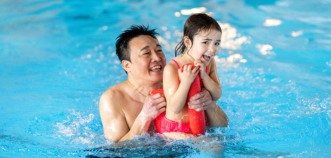 Glückliches Mädchen mit Vater im Wasser. Badespass mit Poolnoodle.